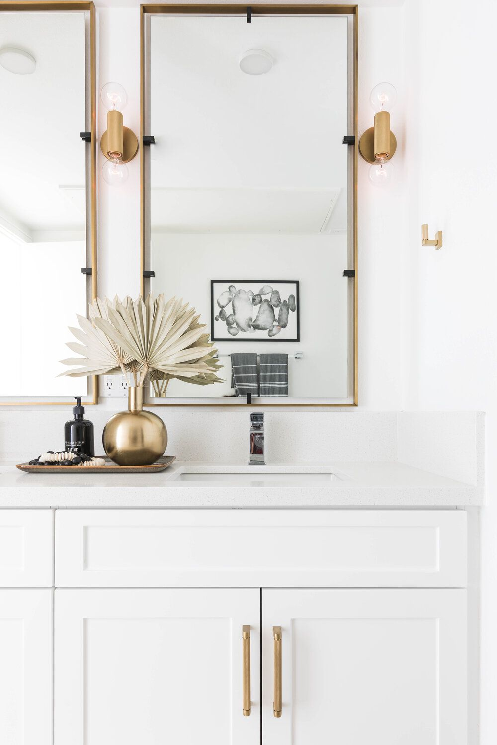 A bathroom vanity topped with small decor organized on a sleek gold tray