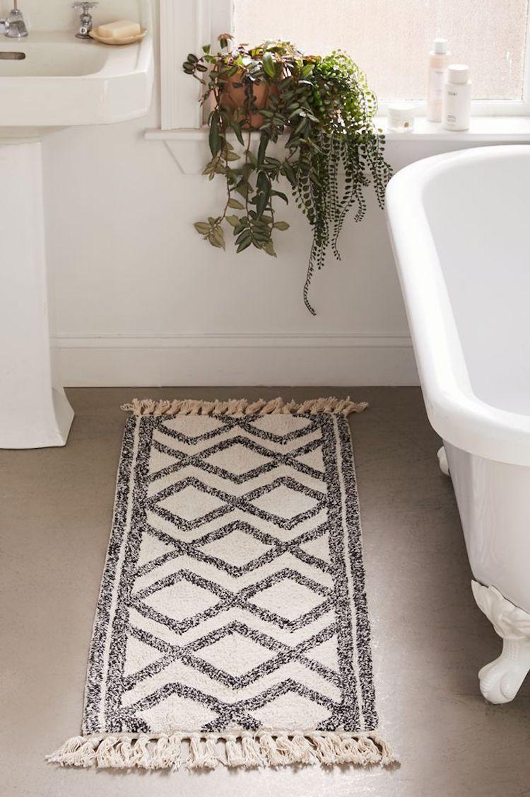 A gray and white printed bath mat in a bathroom