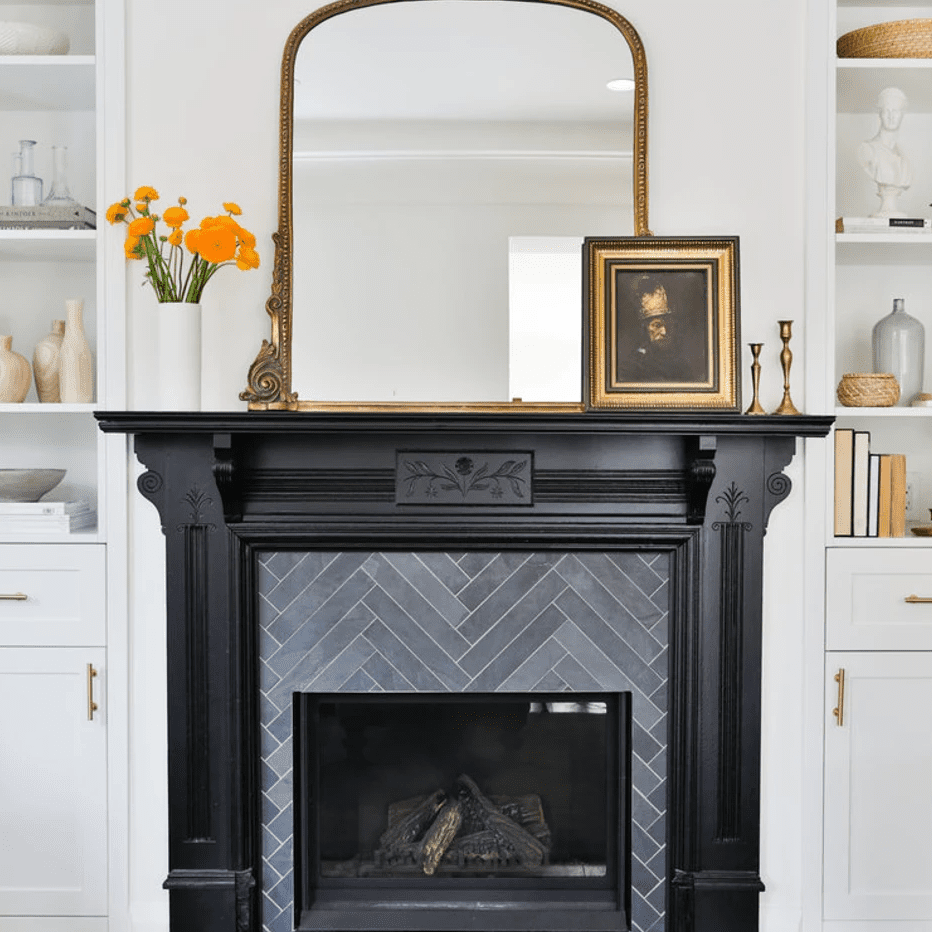 A living room with a fireplace made of slate gray tiles and a black mantle
