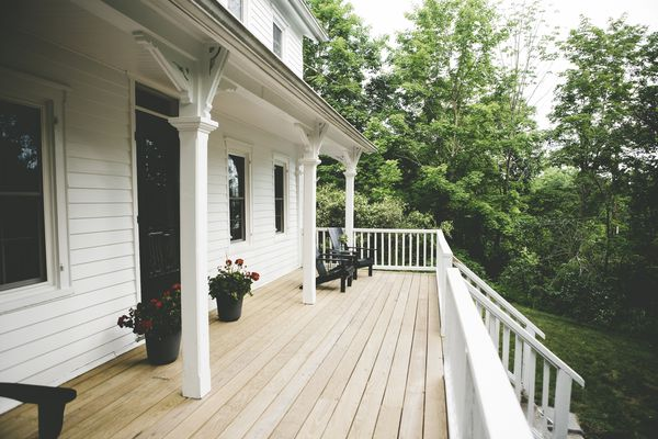 The large front porch of a white farmhouse