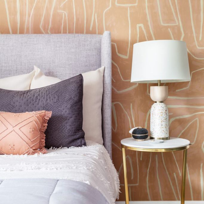 Bedroom with purple bed and bold peach-colored wallpaper