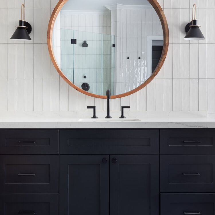 A bathroom with navy cabinets and a white tiled backsplash