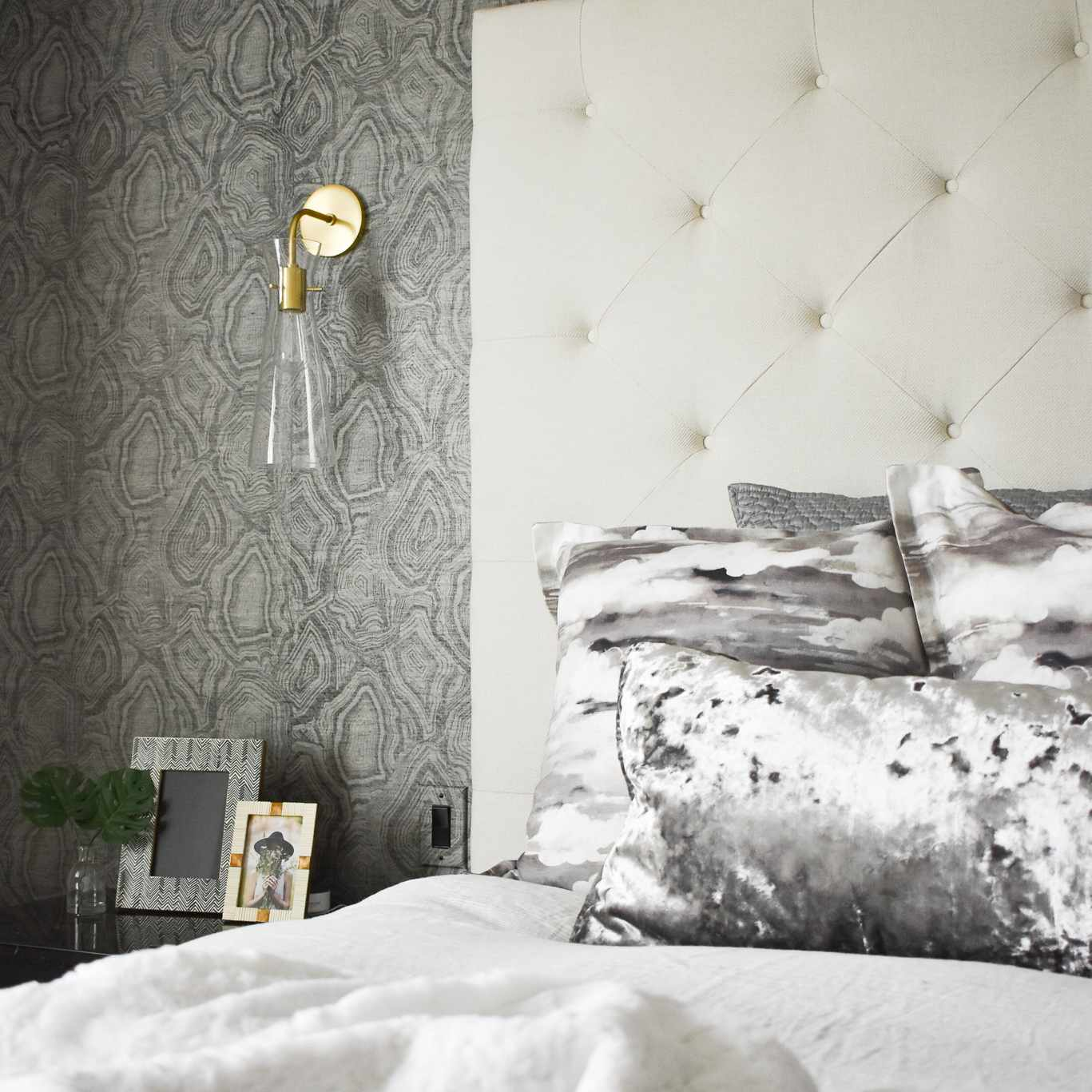 Close-up of bed with gray satin pillows.