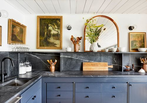 An art-filled kitchen with marble countertops