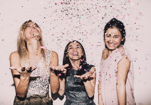 Three friends smiling, acting positive, and having fun by throwing confetti.