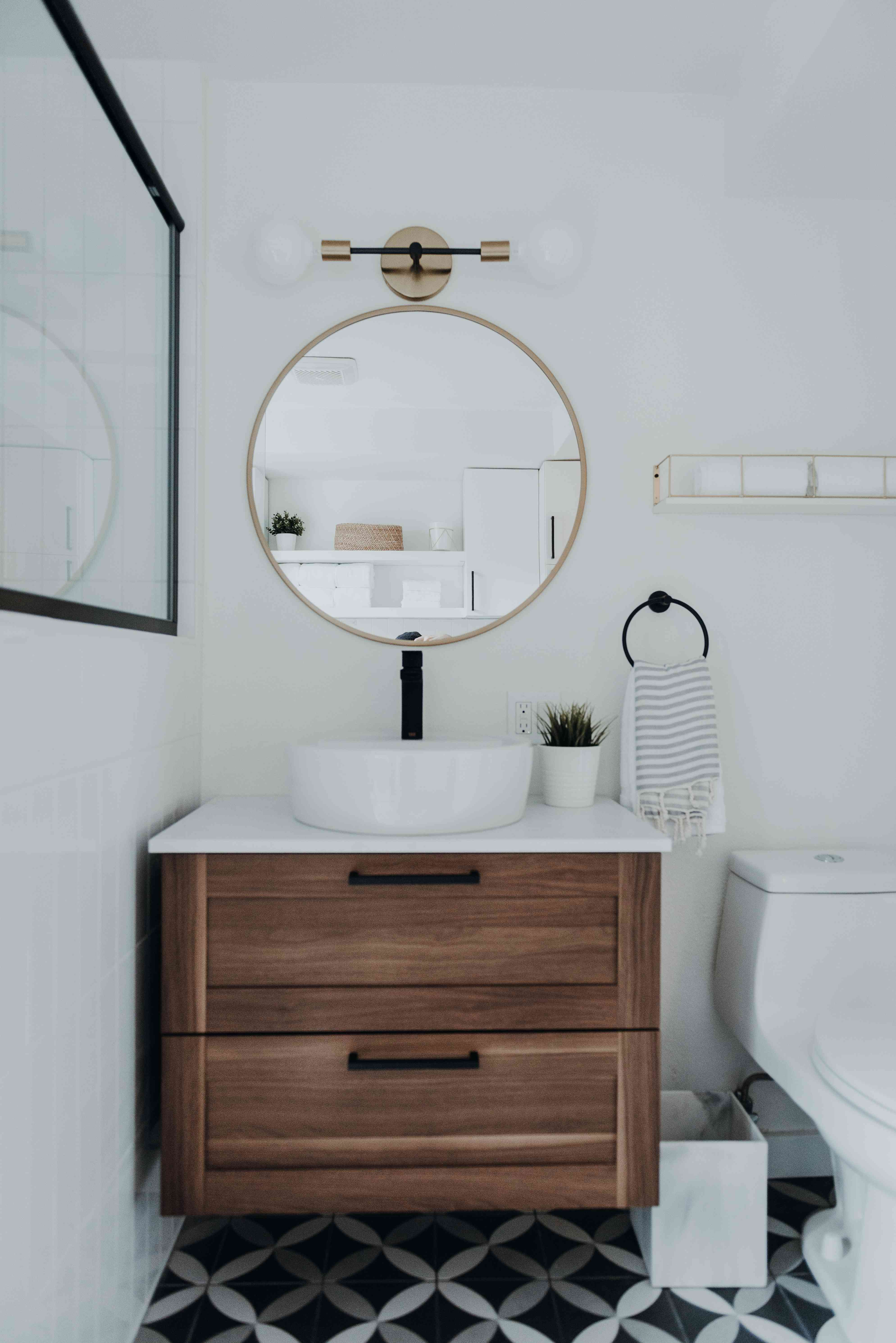 bathroom with tiled floor and gold mirror