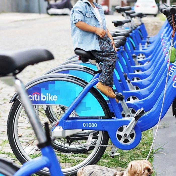 una niña en bicicleta y un perro con correa