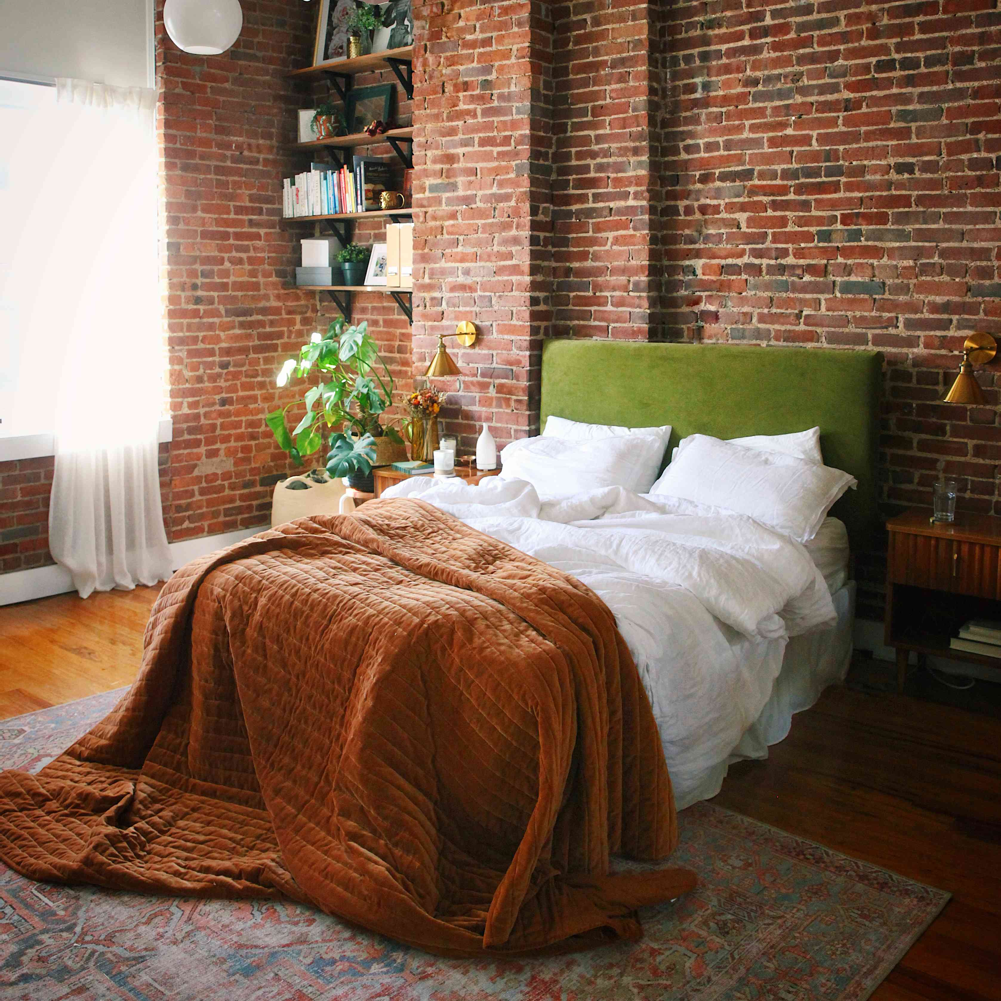 Bed with green headboard in front of brick wall.