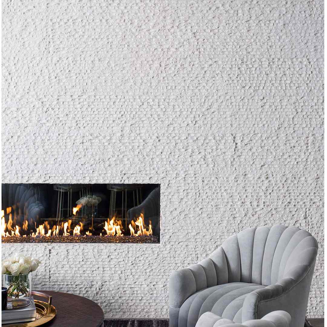 Fireplace with two powder blue accent chairs, white textured wall