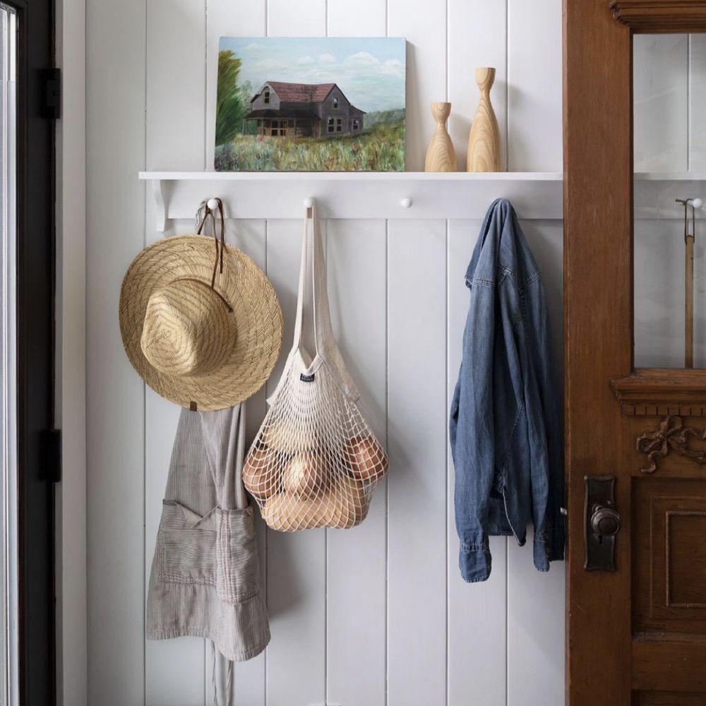 Jacket, apron, and denim jacket hanging from white peg rack