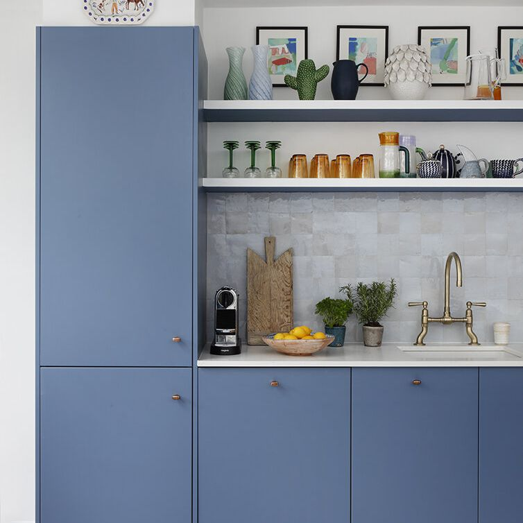 A kitchen with blue cabinets and an iridescent backsplash