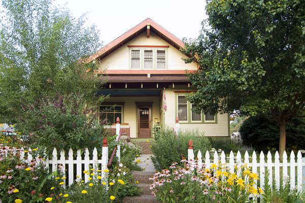 A quaint arts and crafts-style bungalow with a white picket fence and flowering garden