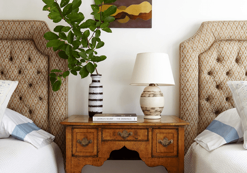 A bedroom with tufted headboards and an antique nightstand