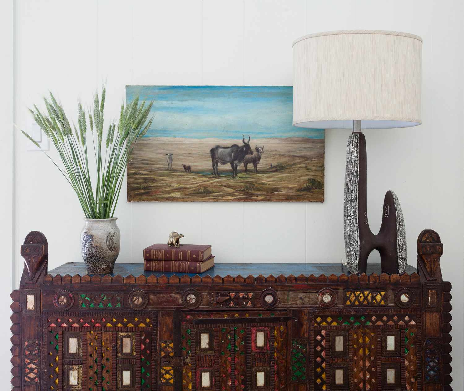 A bedroom decorated with Western art, furniture, and decor