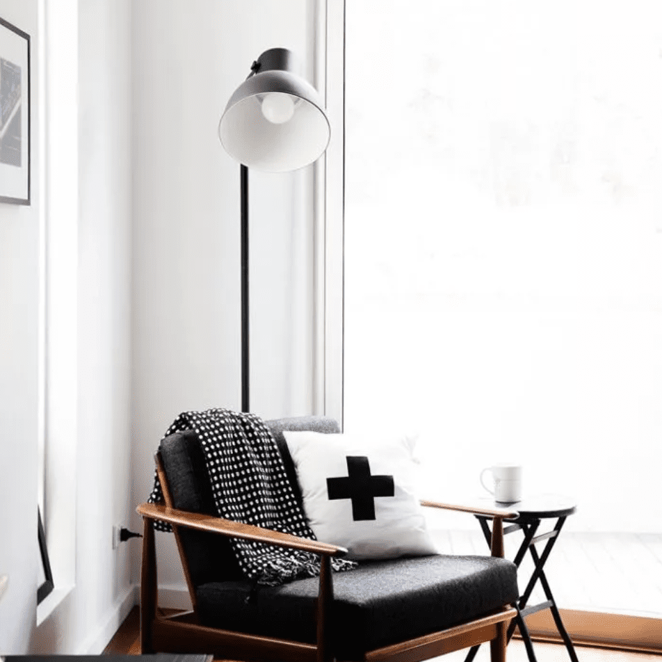 A black floor lamp sits above a chair in a corner