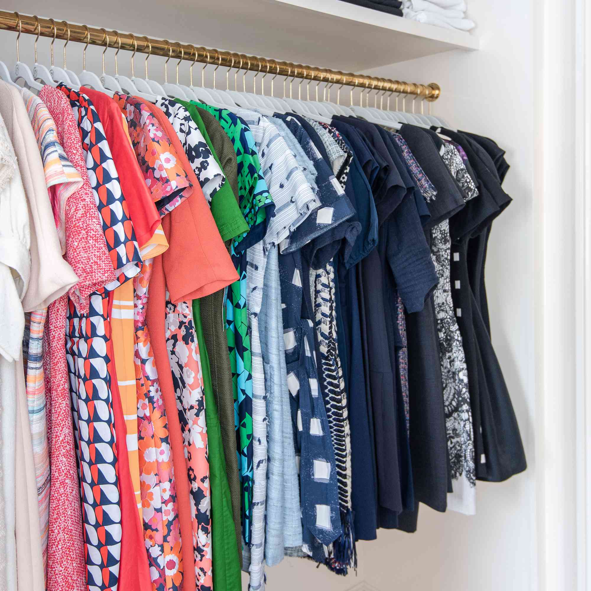 Closet with dresses organized by color