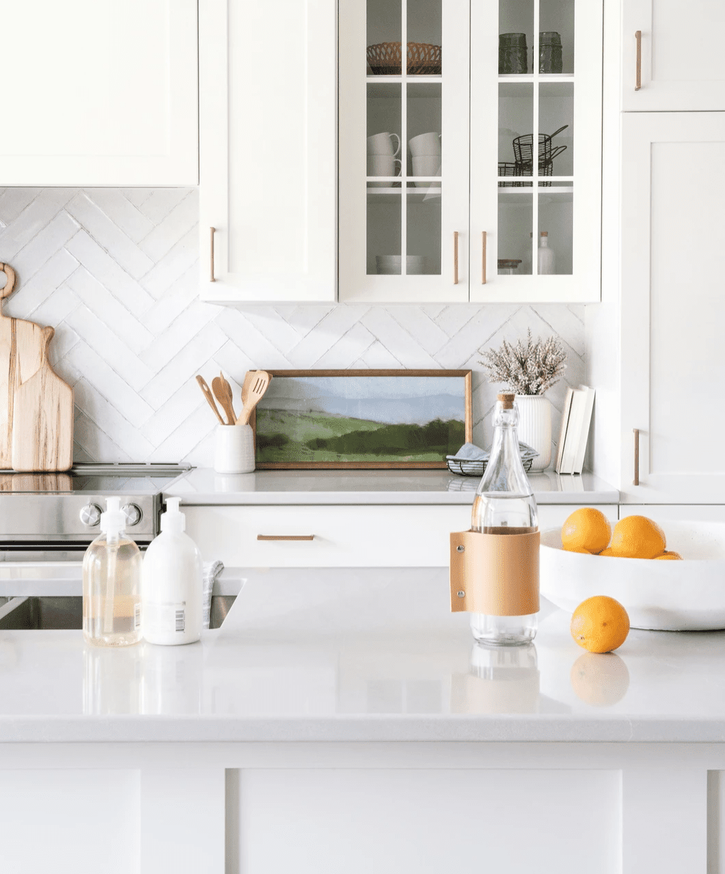 A light-filled kitchen with white cabinets, countertops, and a white tile backsplash