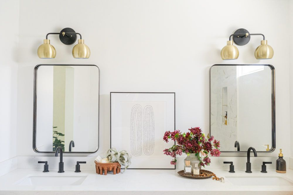 White bathroom with brass sconces