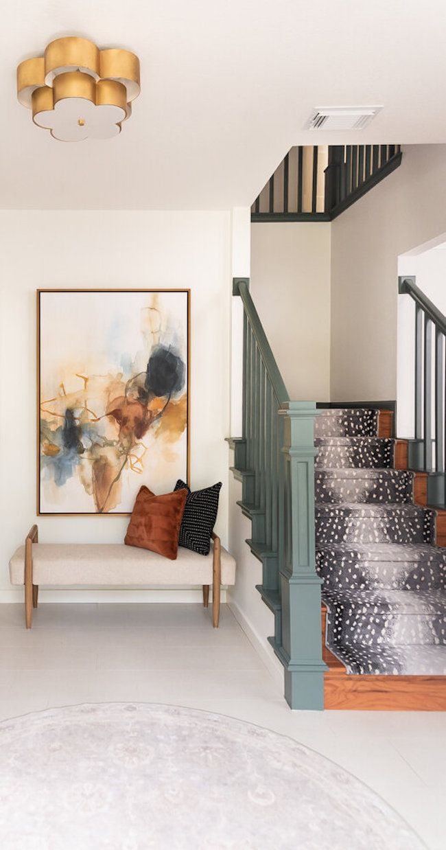 entryway with seating, artwork and painted railing of staircase and decorative rug on stairs