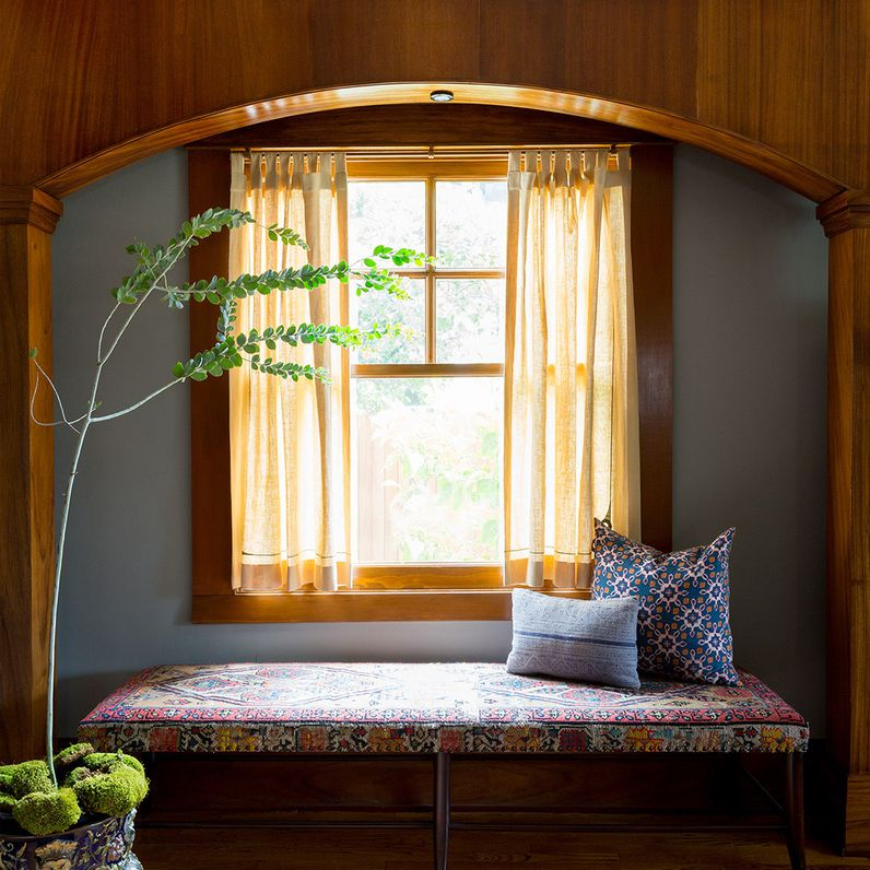 Arched wood paneling in front of a window nook