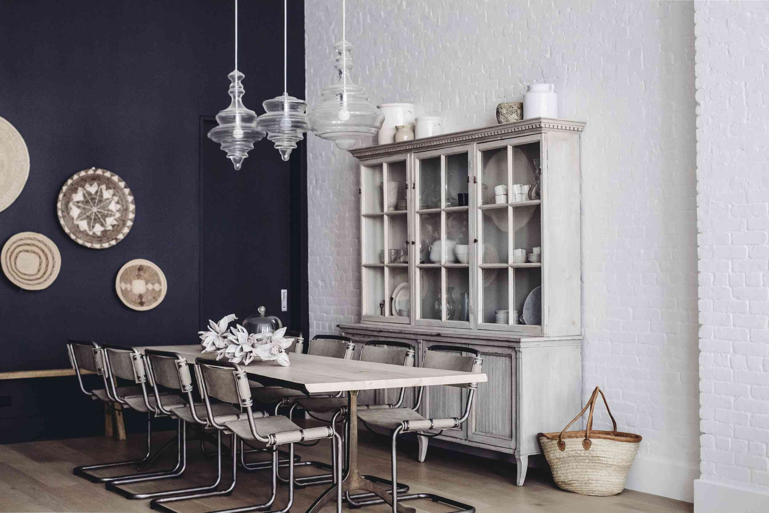 A navy and white dining room lit with three coordinated (but slightly different) pendant lights