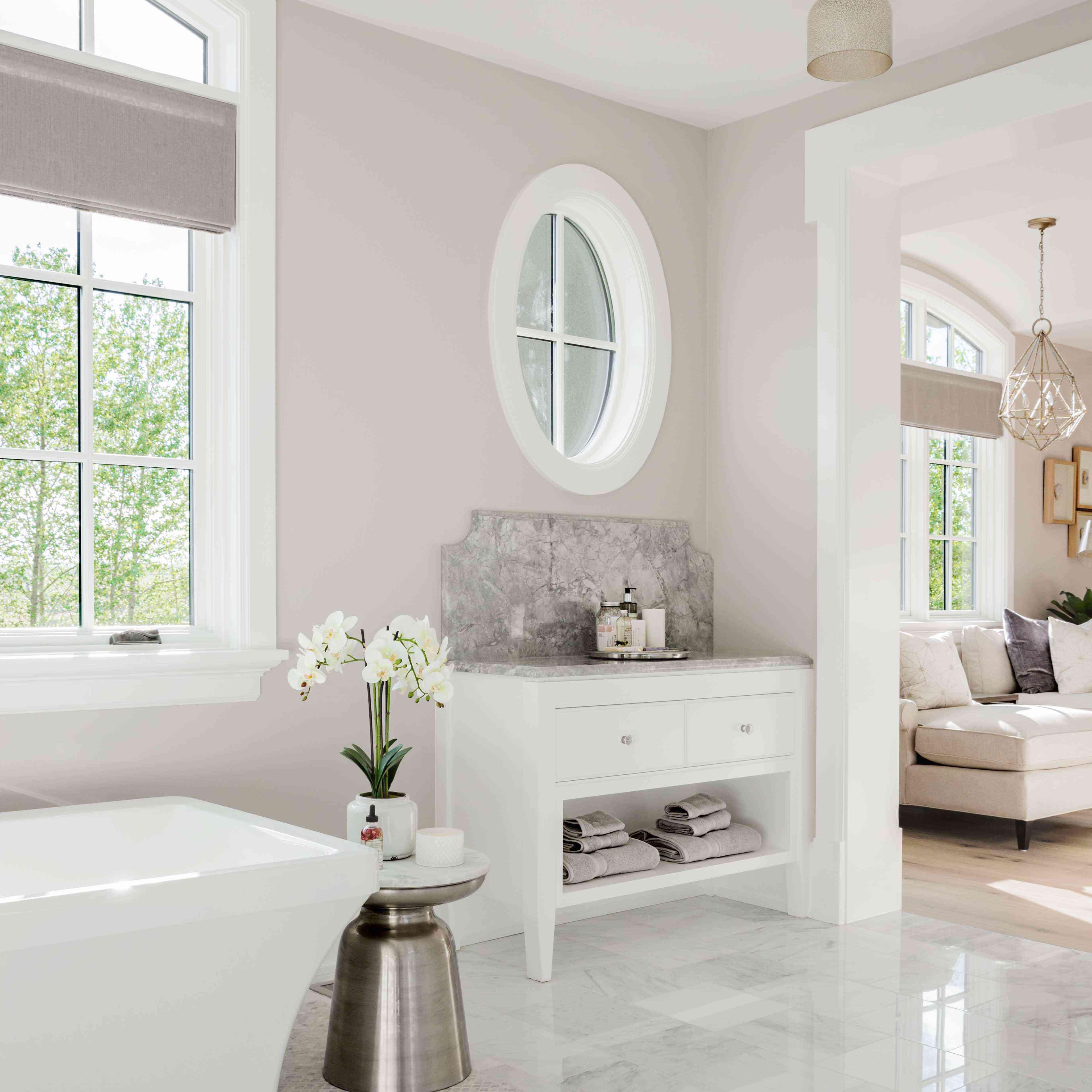Spacious bathroom features marble vanity backsplash, high ceiling