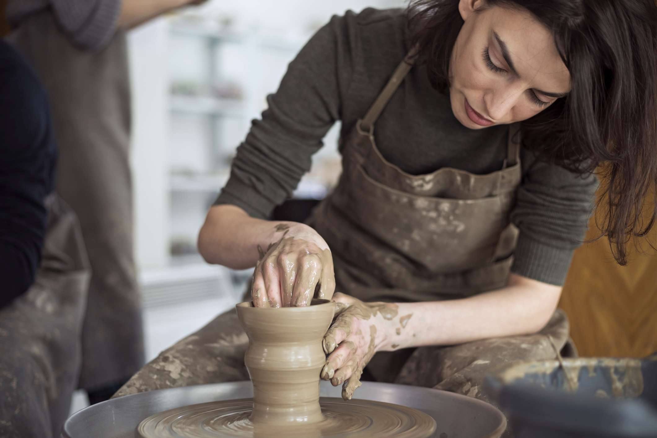Woman works at pottery wheel