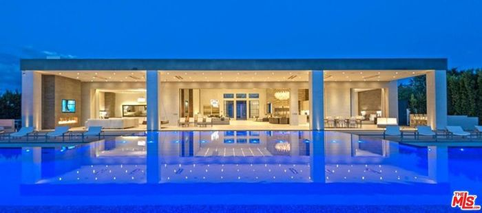 A sweeping view of a home, past the swimming pool, looking into its open-plan living spaces.
