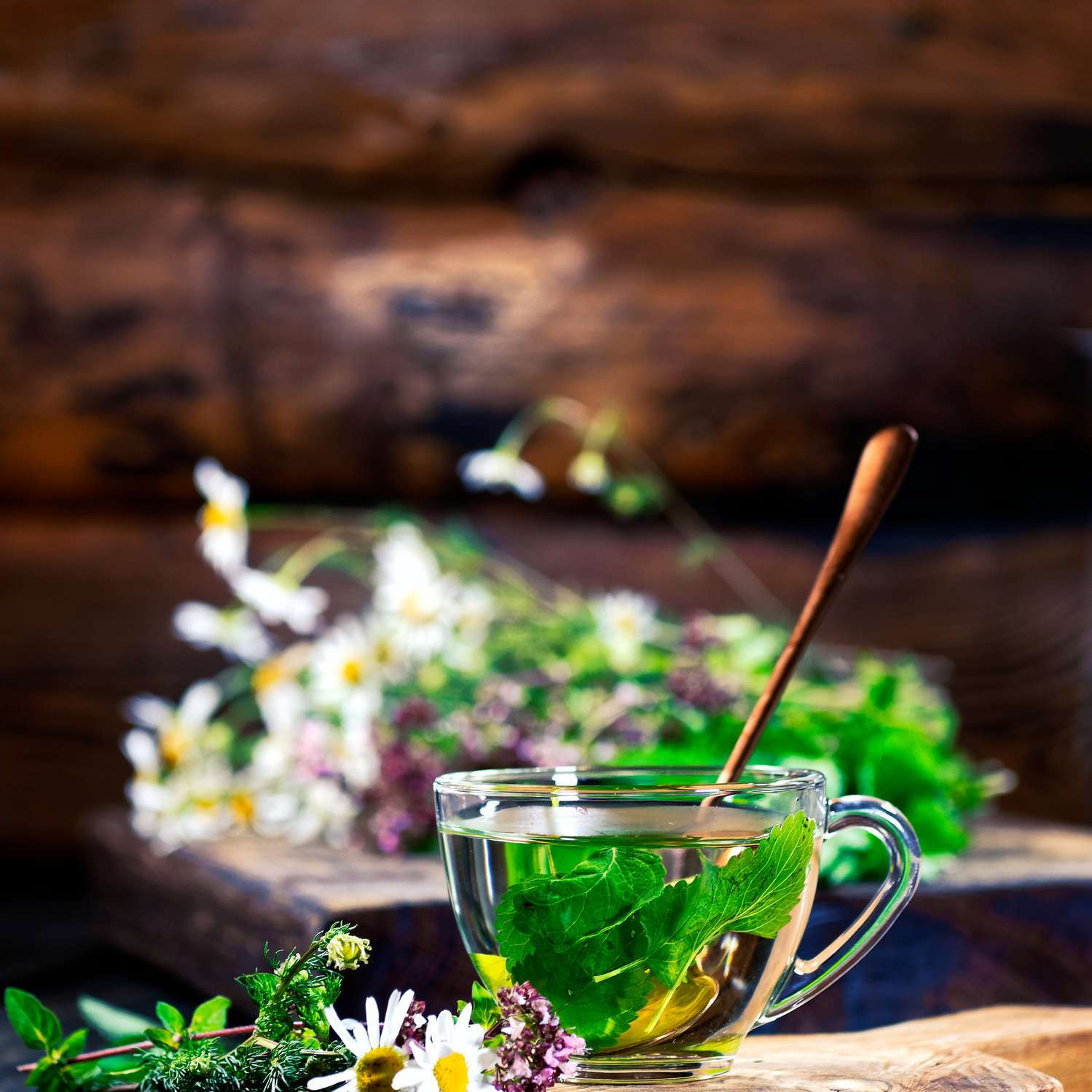 fresh herbs and flowers in clear glass teacup on wood cutting board