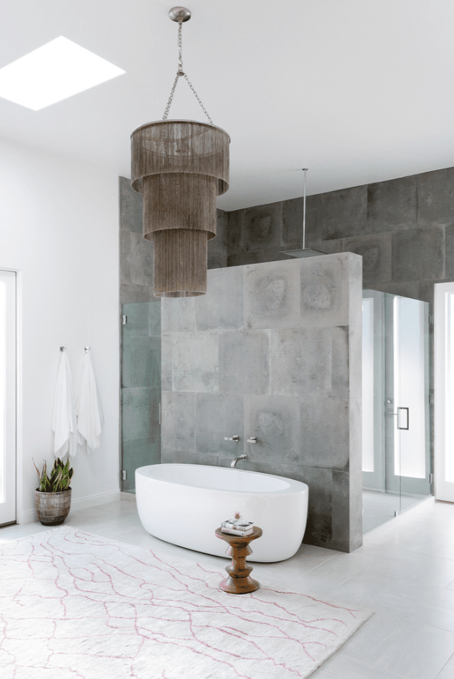 A concrete bathroom with a freestanding tub and a fringe-lined chandelier