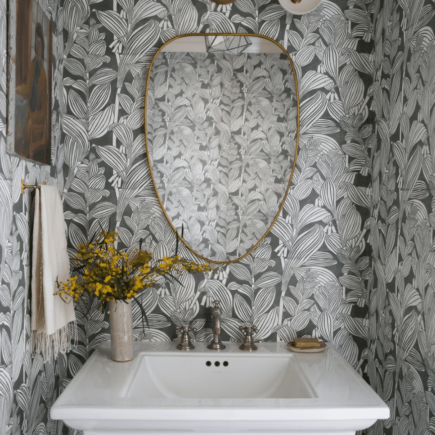 A powder room with a bold mirror, green printed wallpaper, and statement lighting