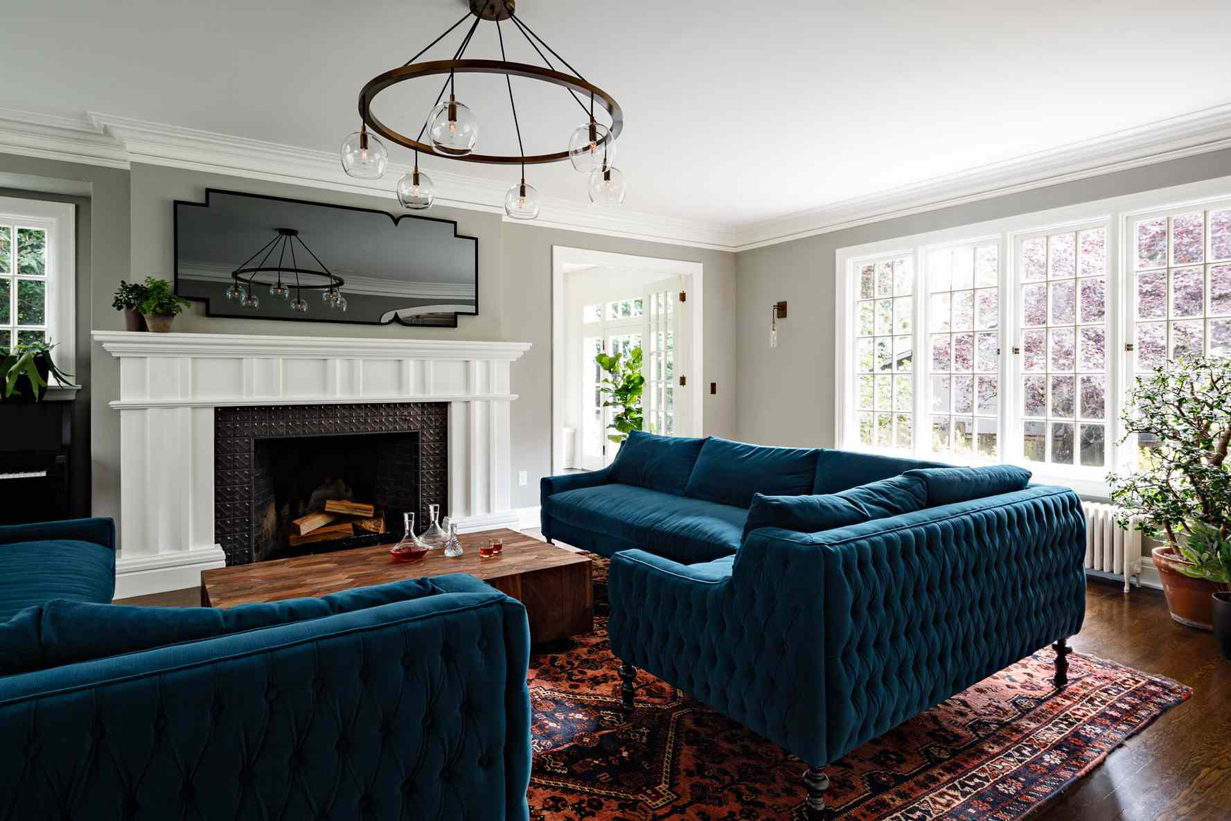 Living room with gray walls, blue couches in Tudor home