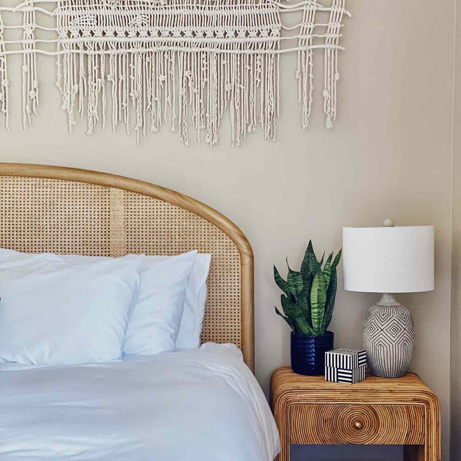 Boho chic bedroom with rattan and can furniture and a woven wall hanging