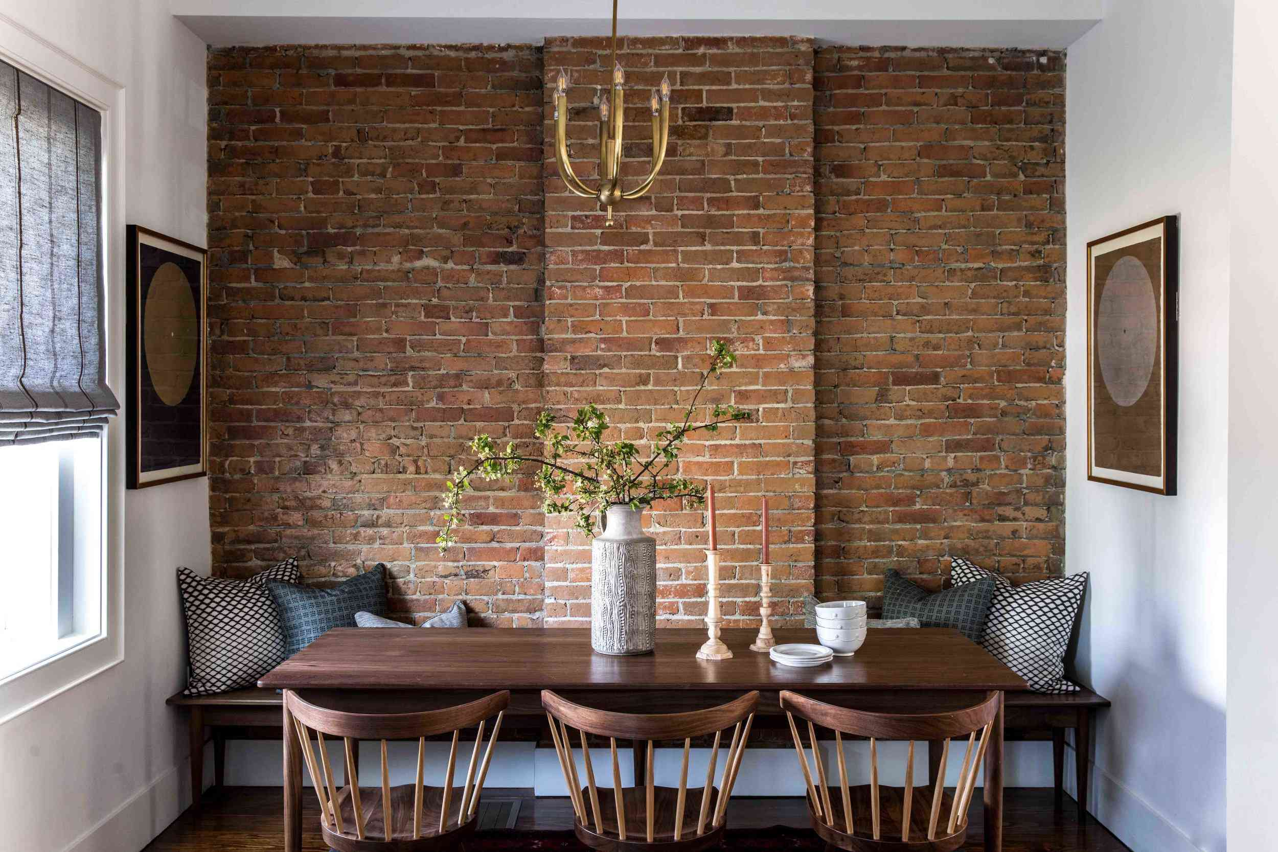 A dining room with high ceilings and a small metal chandelier