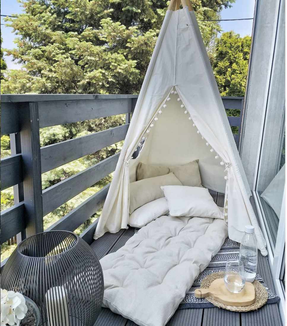 balcony with white tent and cushion with pillows underneath it