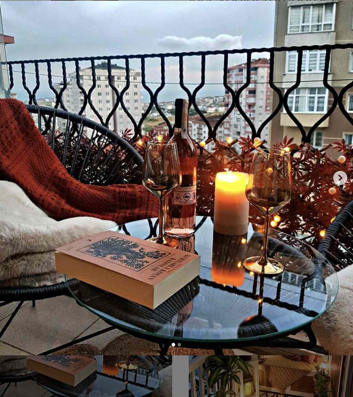 balcony with city views, glass table with two glasses of wine and bottle, candle, and book. Accent chair with blankets draped across.