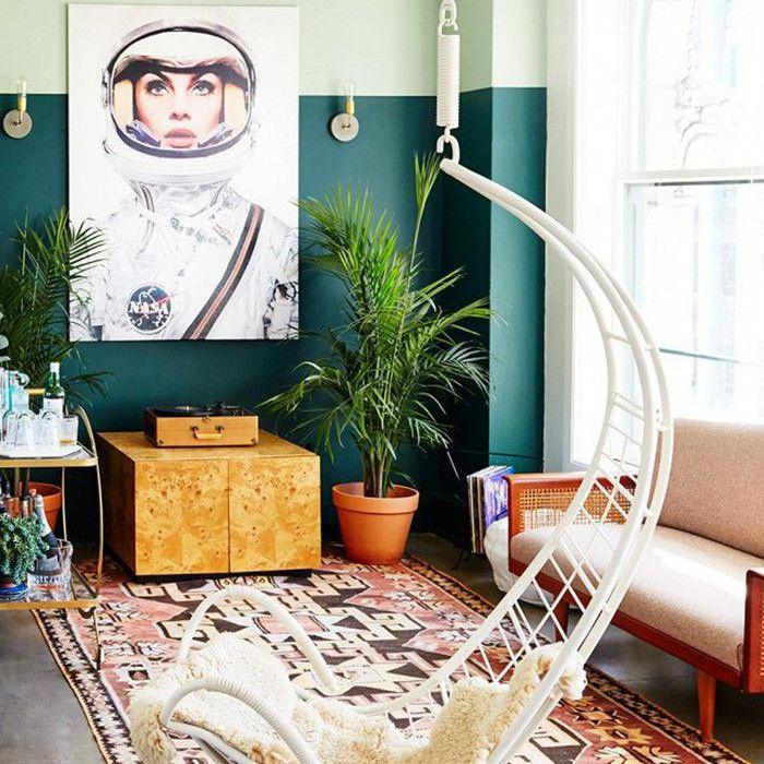 Alfombra llamativa, silla colgante e interesante obra de arte en la sala de estar