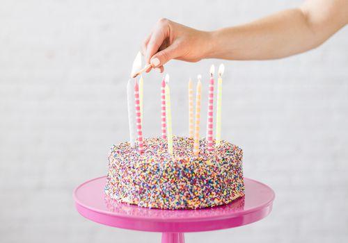 woman lighting candles on a birthday cake