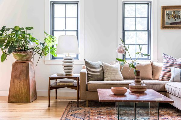 Soft neutral living room with funky lamp and large plant.