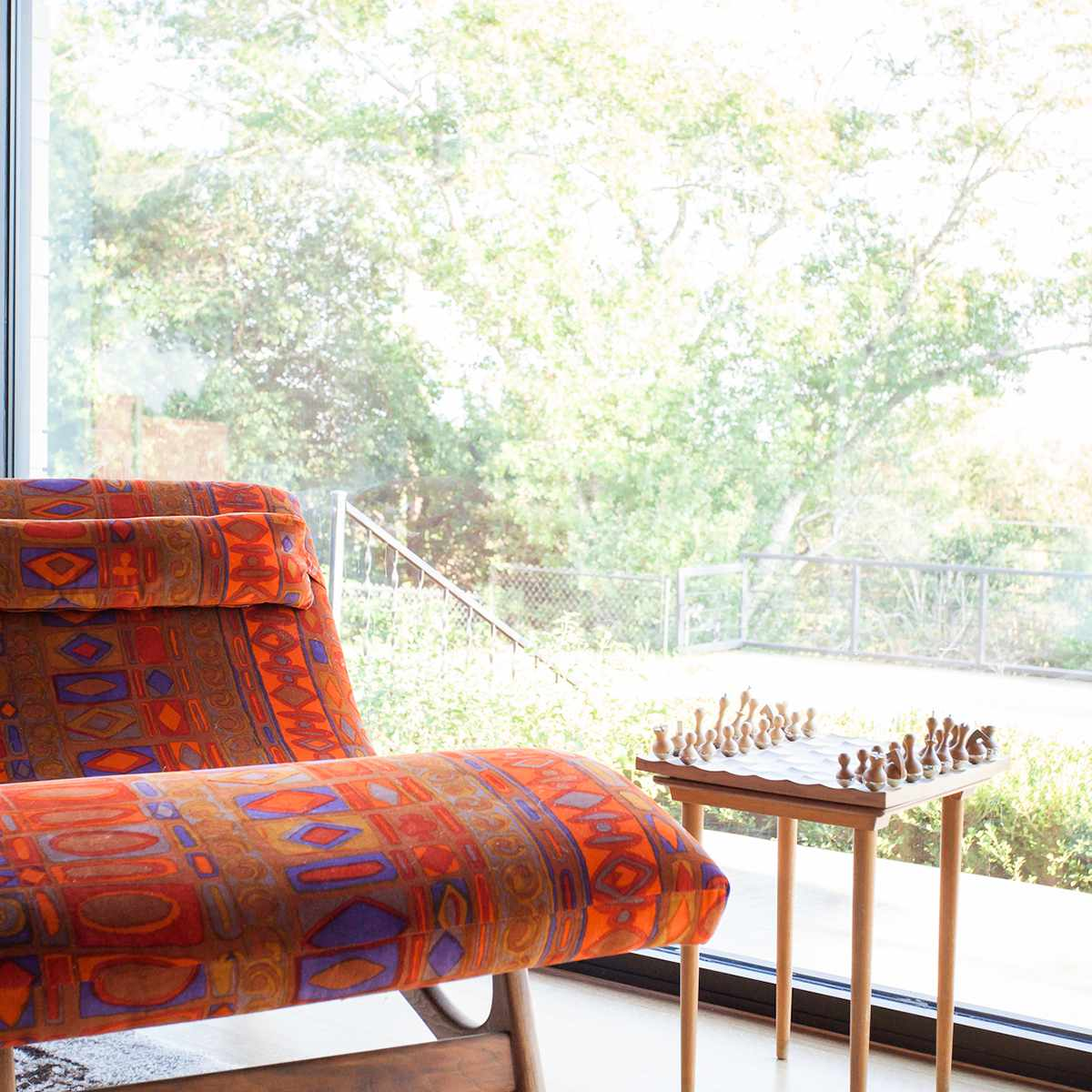 A printed chair next to a chess set