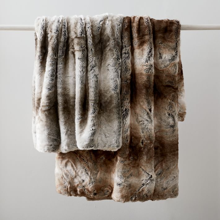 Two faux fur throws hung over a pole