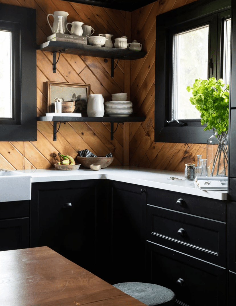 A black kitchen with wood-lined walls