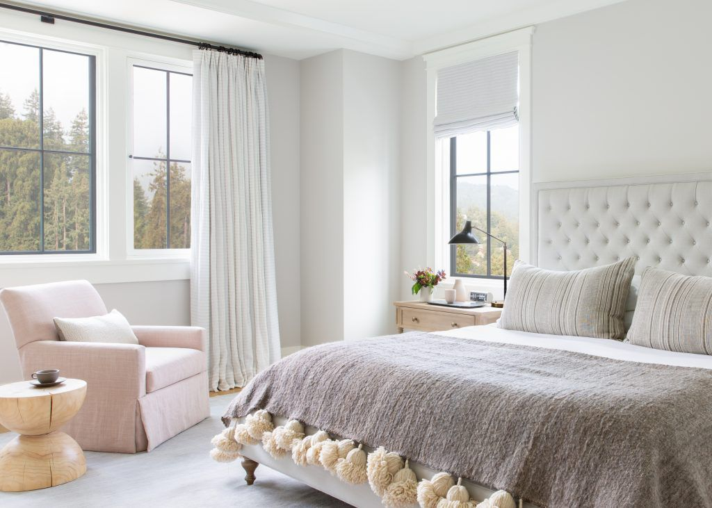 Neutral bed and reading chair in sunny bedroom.