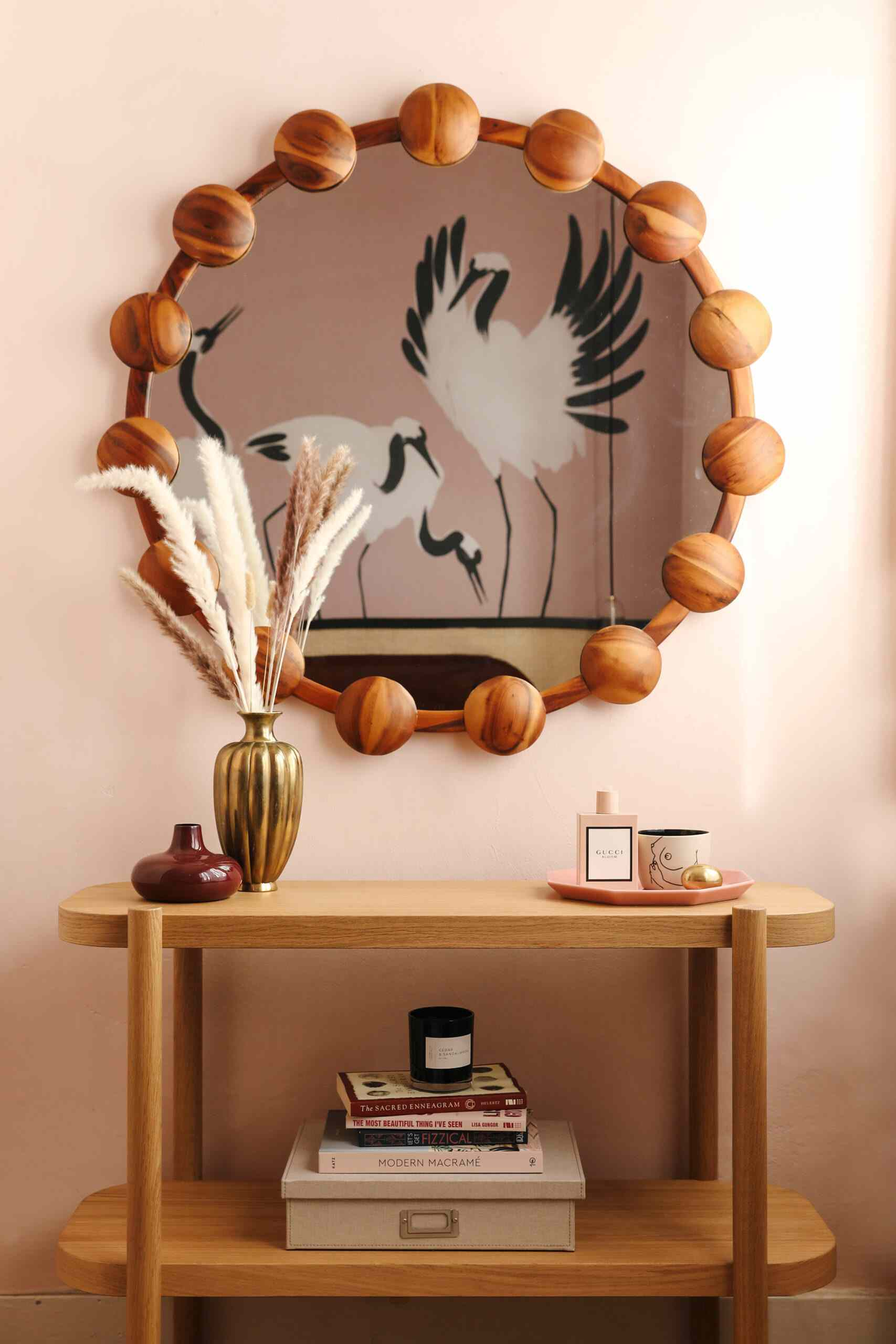 A blush-colored wall paired with light-stained wood decor