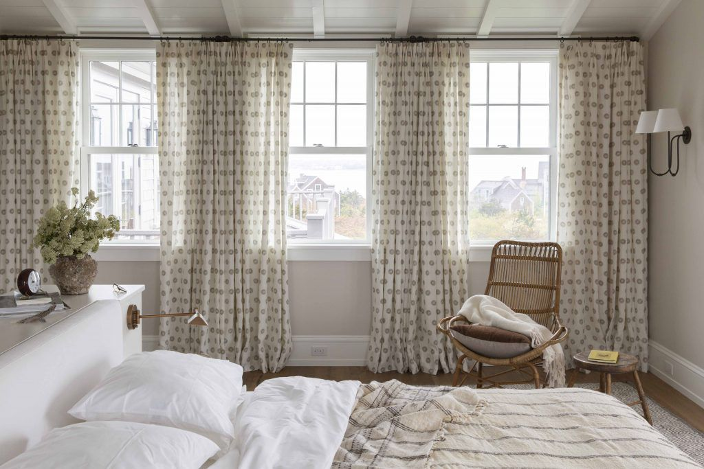 A bedroom with polka dot curtains and striped bed linens