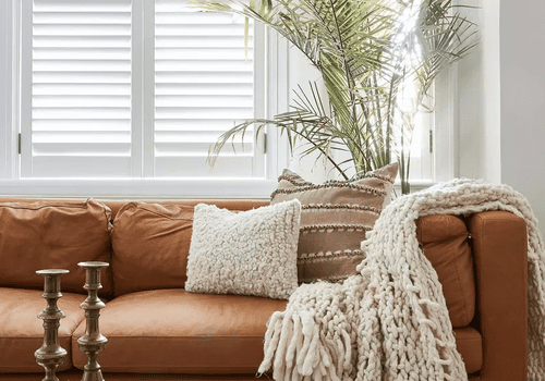 A living room outfitted with a caramel brown leather couch, a beige pillow, and a beige blanket
