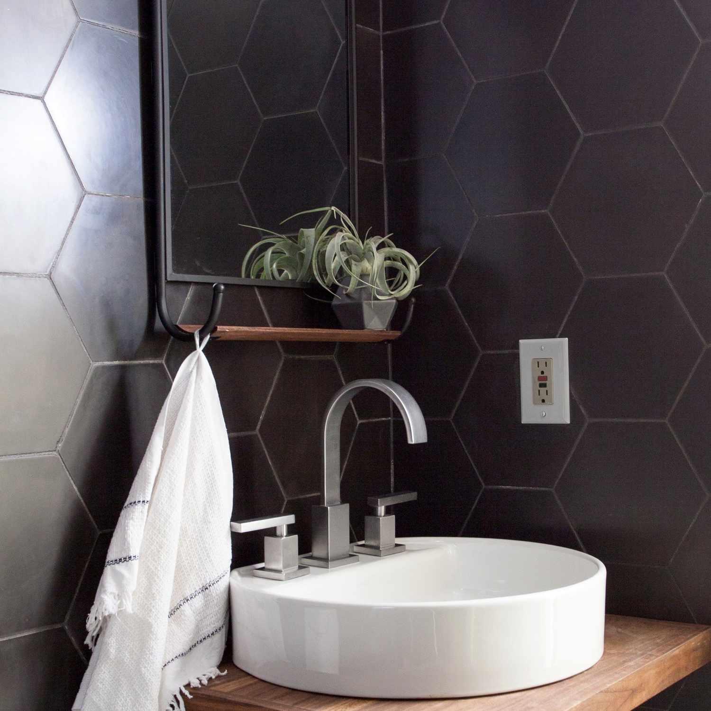 A bathroom lined with black hexagonal tiles