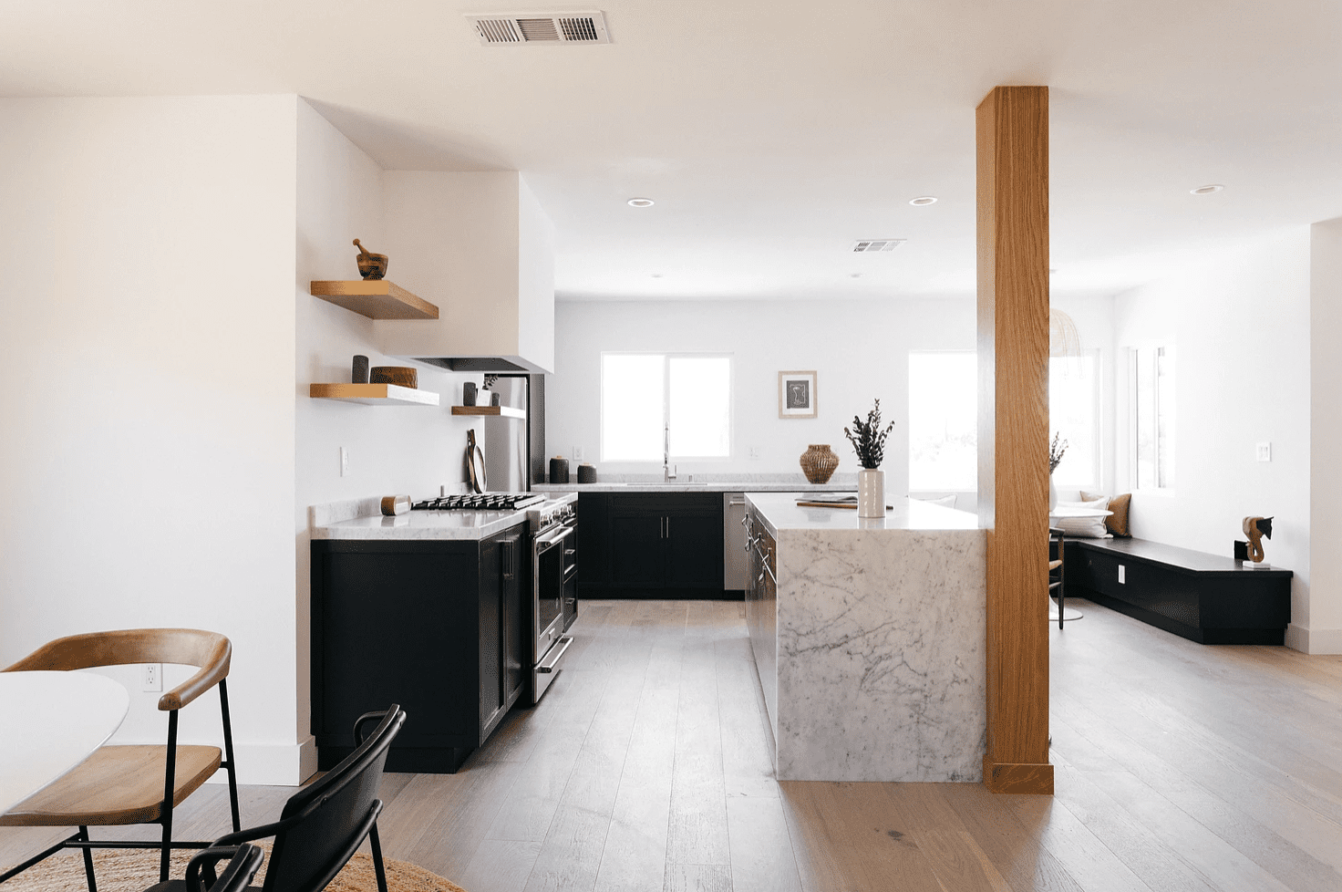 A kitchen with a marble bar next to a wood column