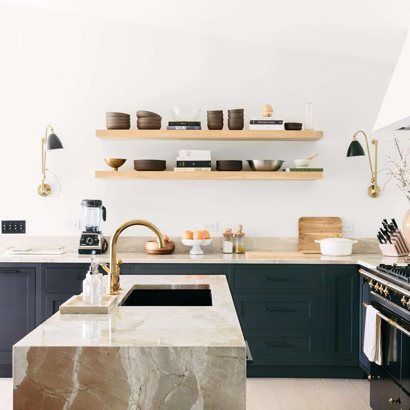 A sleek kitchen with wooden shelves topped with minimalist dinnerware and cookbooks