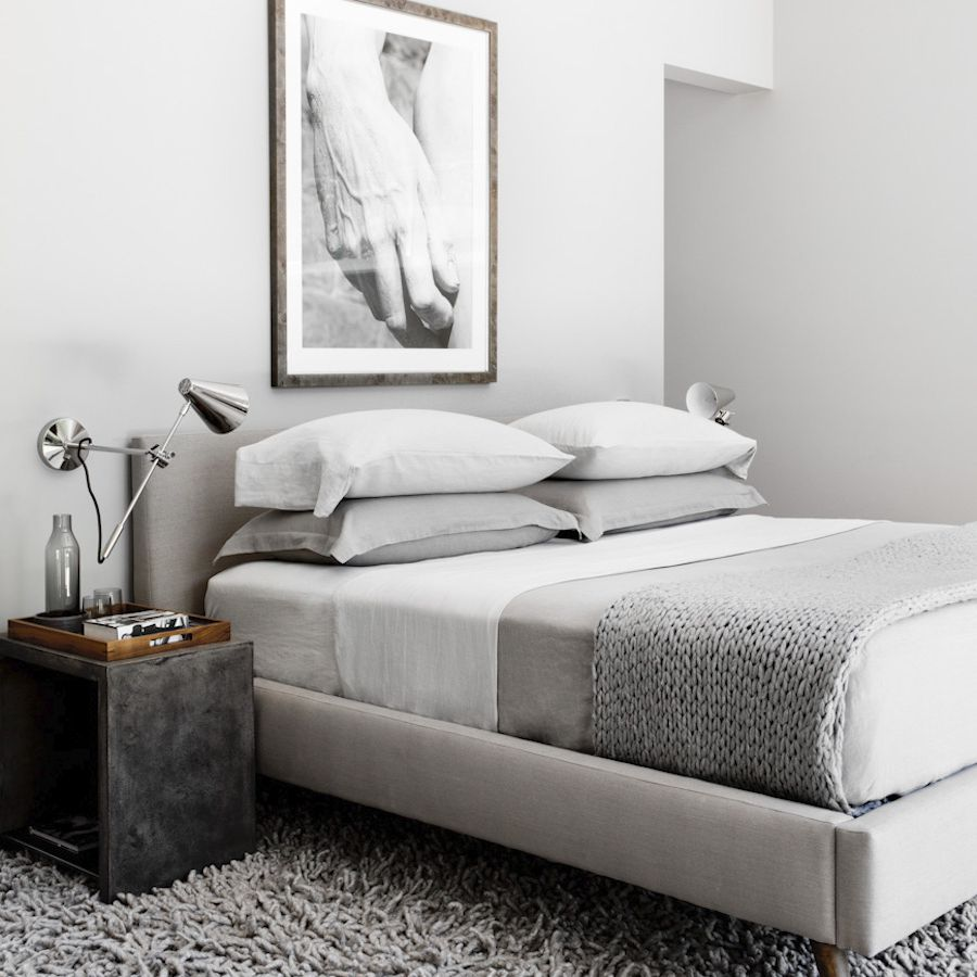 An all-gray bedroom with sleek silver sconces